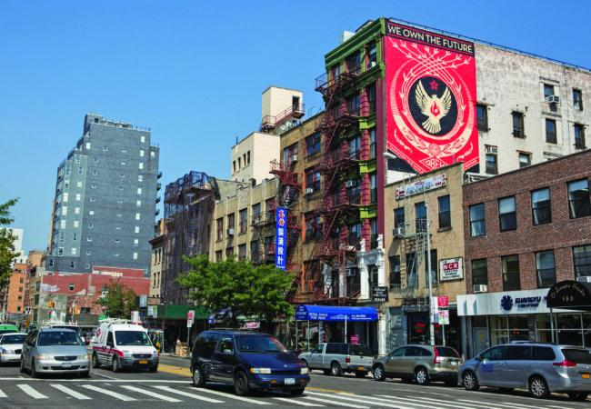 """NEW YORK, NY - AUGUST 27:  Street artist Shepard Fairey's new mural is seen on a building at 161 Bowery on August 27, 2014 in the Lower East Side Neighborhood of New York City. The mural reads, """"We Own The Future, Transform Our World With Creative Response.""""  (Photo by Andrew Burton/Getty Images)"""
